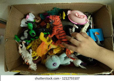 Children playing with toys in a box. lots of toys, colorful toys, children taking the toy, cute hand, small hand