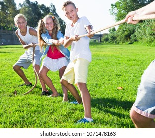 Children playing tug of war during joint games outdoors on sunny day