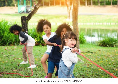 Children playing tug of war at the park, Group of children in a field trips.