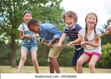 Photo of Children playing tug of war at the park