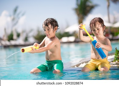 Children playing with water guns in swimming pool