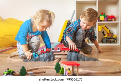 Children playing with wooden train. Boy and toddler girl play with railroad and cars. Educational toys for preschool and kindergarten child. Cute kids at home or daycare interior