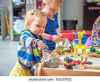 Children playing with wooden train. Toddler boy and baby girl play with crane, train and cars. Educational toys for preschool and kindergarten child. ?ute kids build toy railroad at home or daycare.