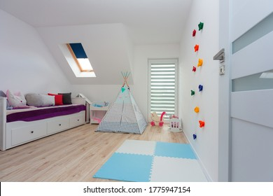 Children playroom with climbing wall and a tent