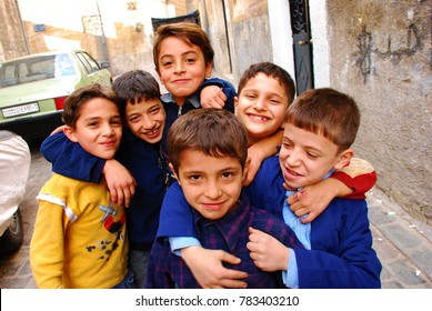 Children pose for a photo on the street in front of their school. Syria before the war. Aleppo, Syria, Middle East. November 9, 2008.