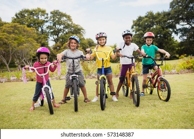 Children posing with bikes in the park