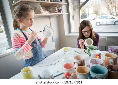 Children at pottery workshop painting pottery