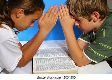 children praying over the bible
