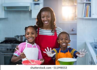 Children preparing cake with their mother in kitchen