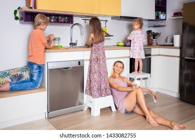 Children preparing diner in the kitchen while mother resting at the kitchen floor.Family life concept