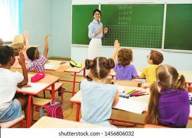 children preschoolers pull up their hands to answer the teacher's question on the background of the blackboard and the classroom in primary school. Back to school, education