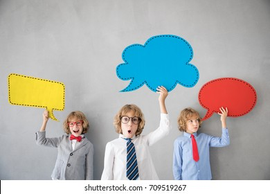 Children pretend to be businessman. Business team of kids. Child playing at home. Imagination, idea and successful teamwork concept. Colored paper speech bubbles with copy space for your text