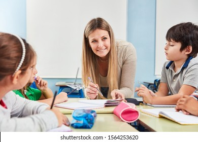 Children of a primary school receive tutoring lessons from a teacher