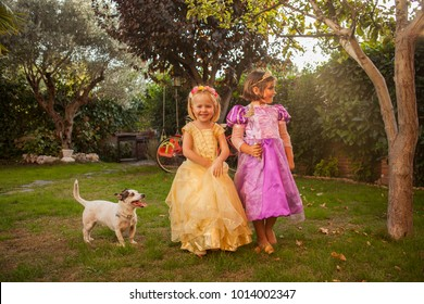 Children in princess costumes playing in the garden. Outdoors.