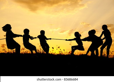Children pulling rope, tug war, sunset, group, copy space
