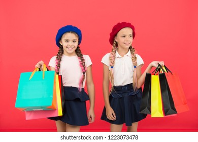 Children pupils satisfied by shopping red background. Obsessed with shopping and clothing malls. Shopaholic concept. Signs you are addicted to shopping. Kids cute schoolgirls hold bunch shopping bags.
