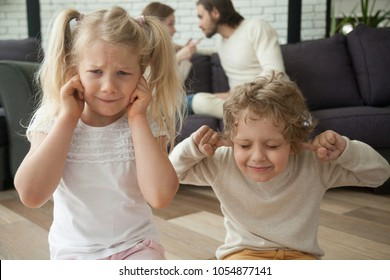 Children put fingers in ears during parents fight at home, sad stressed son daughter feel hurt suffer from psychological mental problem caused by family conflicts arguments, kids and divorce concept
