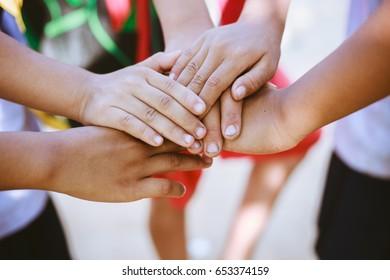 Children putting their hands together.
