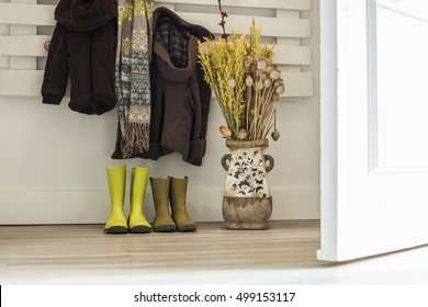 Children rainy boots, brown coats, scarf and a vase with dried flowers. Open door entrance