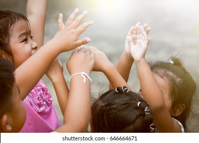 Children raise hands and playing together in the park in vintage color tone