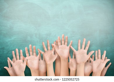 children raised up hands with chalk board
