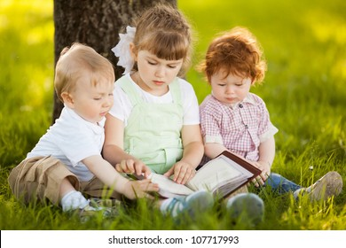 children read a book in park