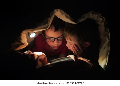 children read a book under a blanket with flashlight. kids secretly reading forbidden literature in the bed