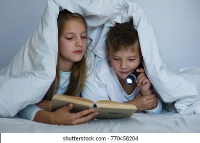 children read the book under the blanket