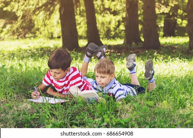 Children reading a book lying on the grass. The boy writes in a notebook.
