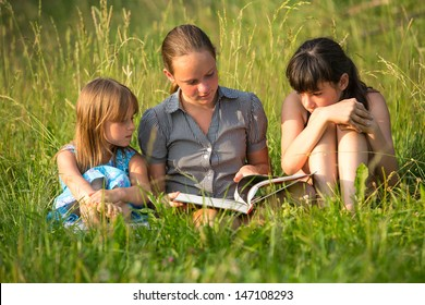 Children reading book in natural environment together.