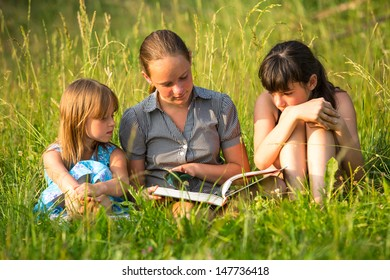 Children reading book on the park together.