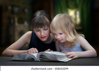 Children reading the book. Two girls, two sisters together. It's dark in the room. Kids fun to read. Evening fairy tale for children at night