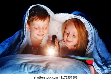 Children reading the book under the blanket