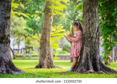 Children reading books at park against trees and meadow in the park.