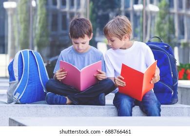 Children reading books. Schoolboys doing homework outdoors.