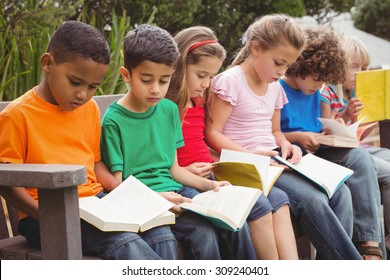 Children reading from books together while sitting down