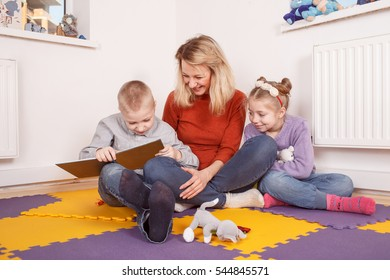 Children reading fairy tale with upbringer in playschool