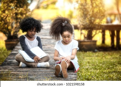 Children are reading happily together in the garden. Soft focus concept.