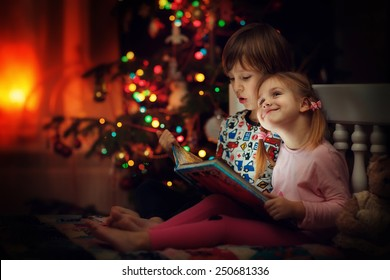 Children reading an interest book sitting on the bed against the decorated Christmas tree