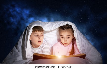 Children reading scary stories in bed before going to sleep. Little girl and boy in pajamas hiding under blanket together. Covered kids with open book not sleep at night. Fear of the dark concept - Shutterstock ID 1443292031