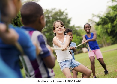 Children and recreation, group of happy multiethnic school kids playing tug-of-war with rope in city park. Summer camp fun