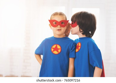 Children in the red and blue suits of superheroes. On their faces are masks and they are in raincoats. They are posing in a bright room.