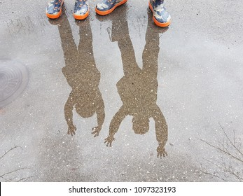 Children reflected in a rain puddle.