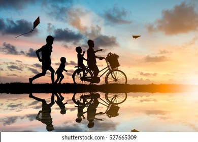 Children ride bikes and chasing paper airplanes and kites have fun. While living with the outside world.Education outside the classroom, family, friends concept.
