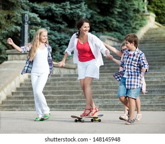 Children ride on a skateboard mom. Young beautiful mother goes on a skateboard.