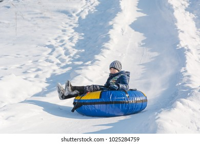 Children ride on tubing. Winter entertainment. Skiing in the winter. Snowy fun in the winter. Fun in the winter. Tubing. People roll on the slides.
