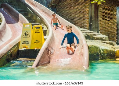 Children ride a water slide in a water park. Happy childhood