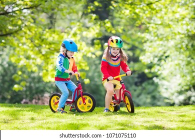 Children riding balance bike. Kids on bicycle in sunny park. Little girl and boy ride glider bike on warm summer day. Preschooler learning to balance on run bicycle in safe helmet. Sport for kids.