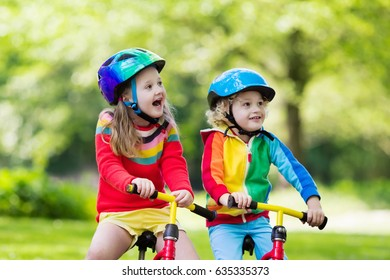 Children riding balance bike. Kids on bicycle in sunny park. Little girl and boy ride glider bike on warm summer day. Preschooler learning to balance on run bicycle in safe helmet. Sport for kids
