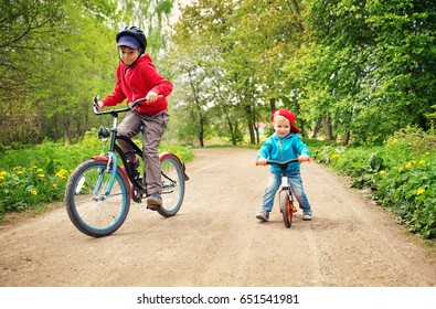 children riding on a bicycles at gravel road in the park in summer